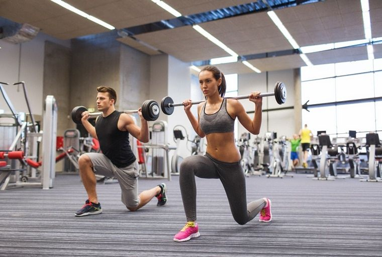 Young man and woman training with barbell